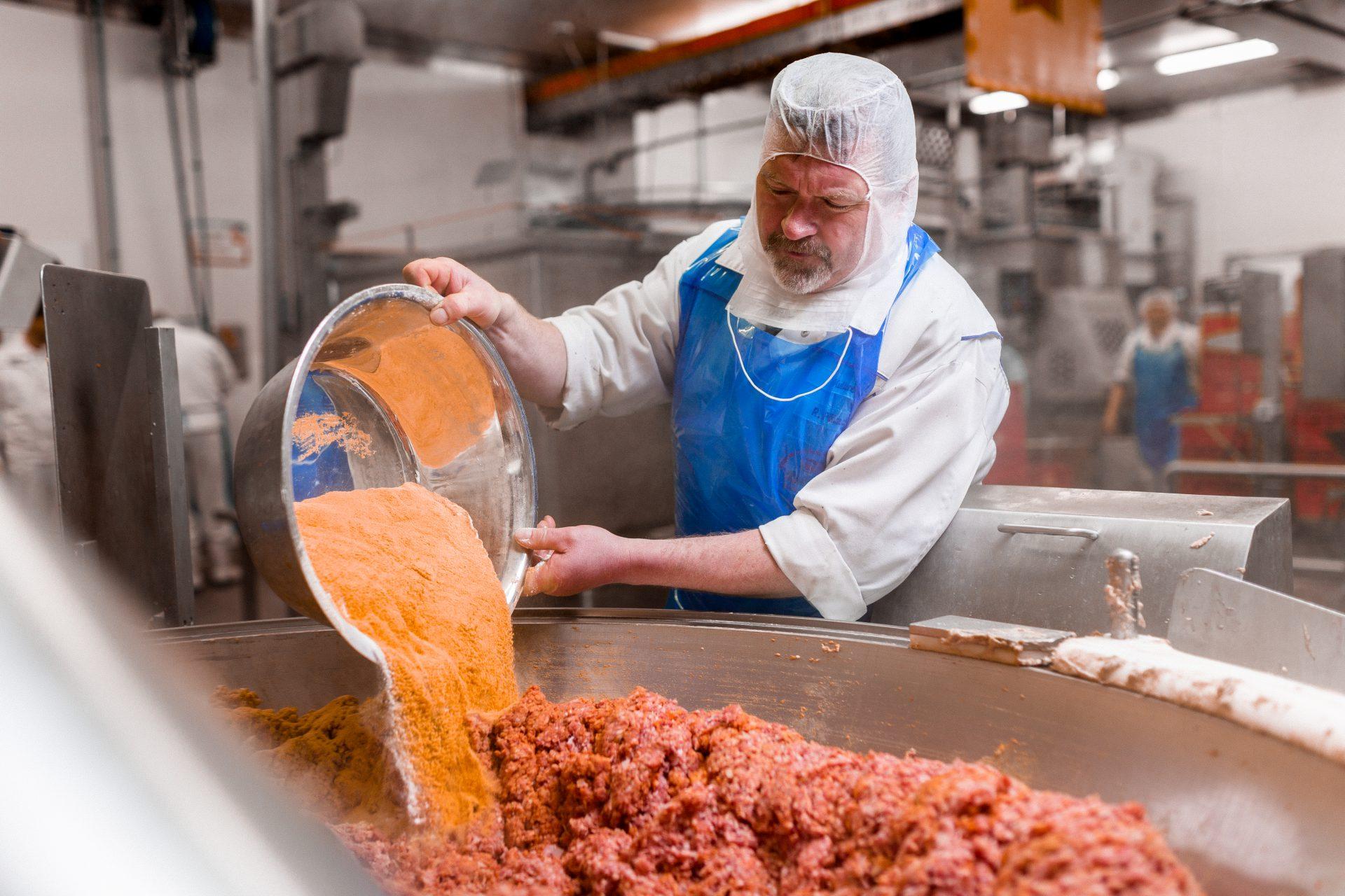 Der Fleischermeister gibt die geheime Würzmischung in den Cutter.