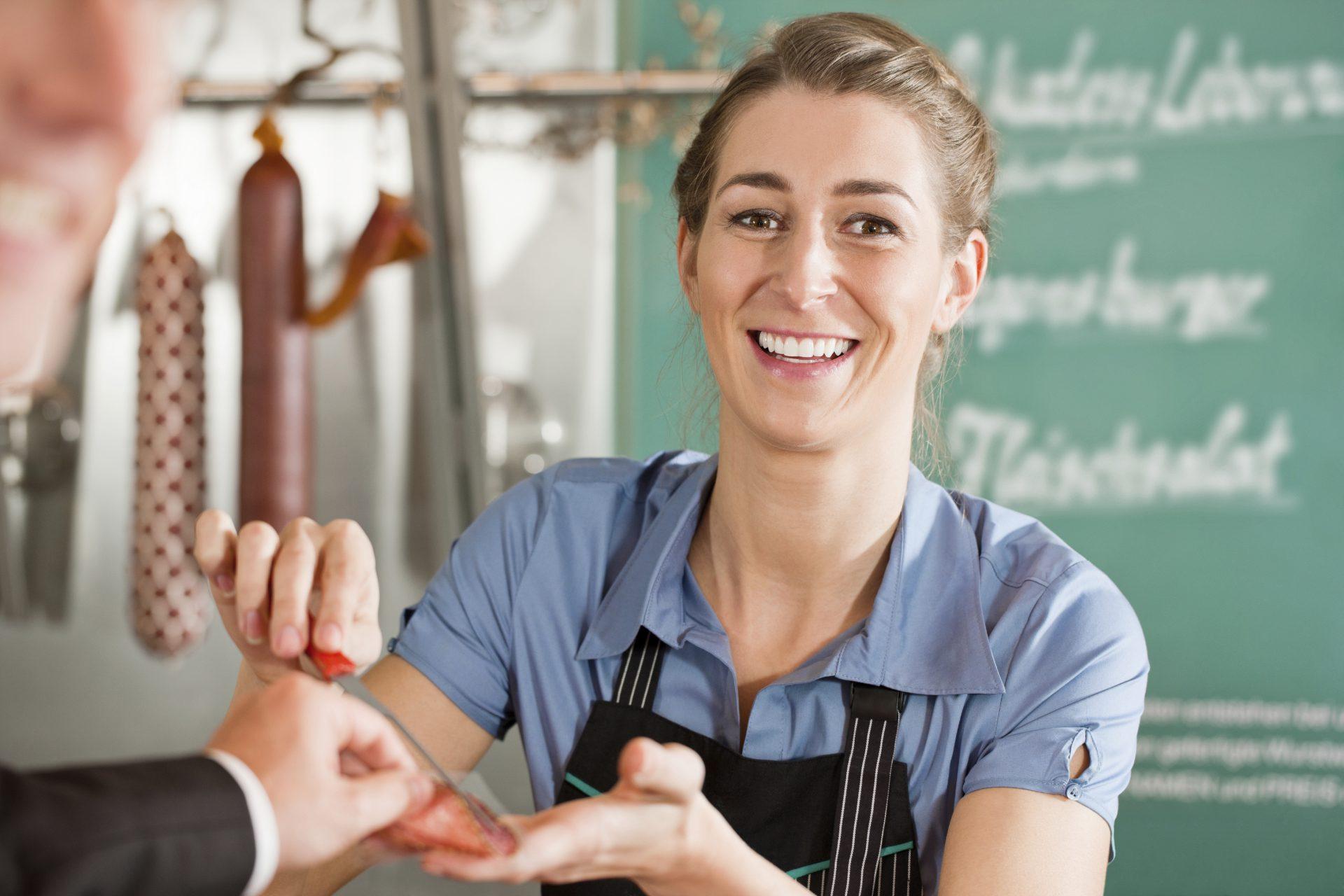Junge Fachverkäuferin für Fleisch- und Wurstwaren bedient einen Kunden