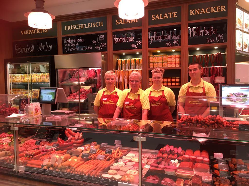 Vier Mitarbeiter hinter der Frischetheke mit dem großen Fleisch- und Wurstangebot