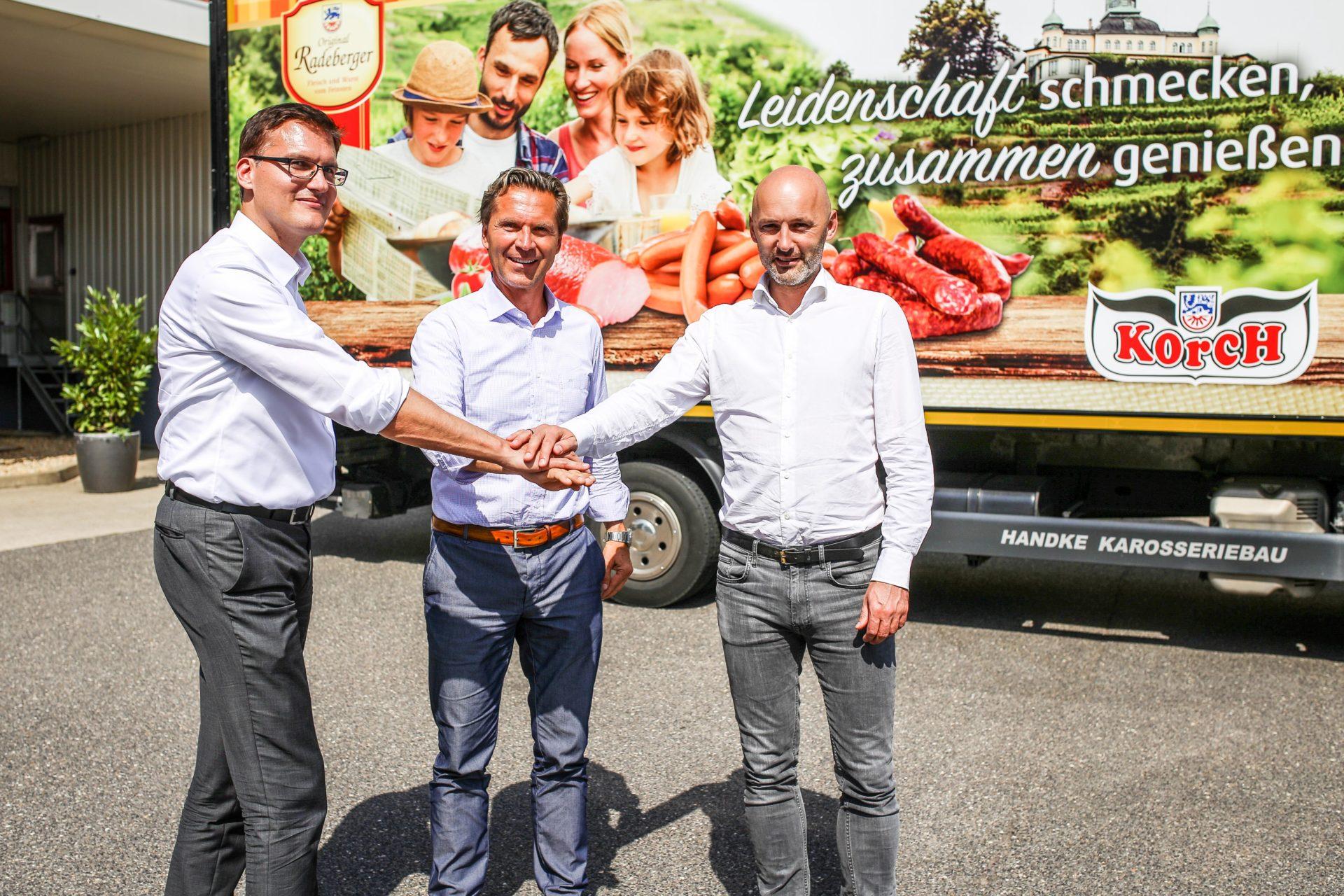 SIB-Geschäftsführer Christian Müller (re.), Michael Korch (m.) und Felix Alber (li.) posieren beim gemeinsamen Handshake vor einem der neuen Lieferfahrzeuge.
