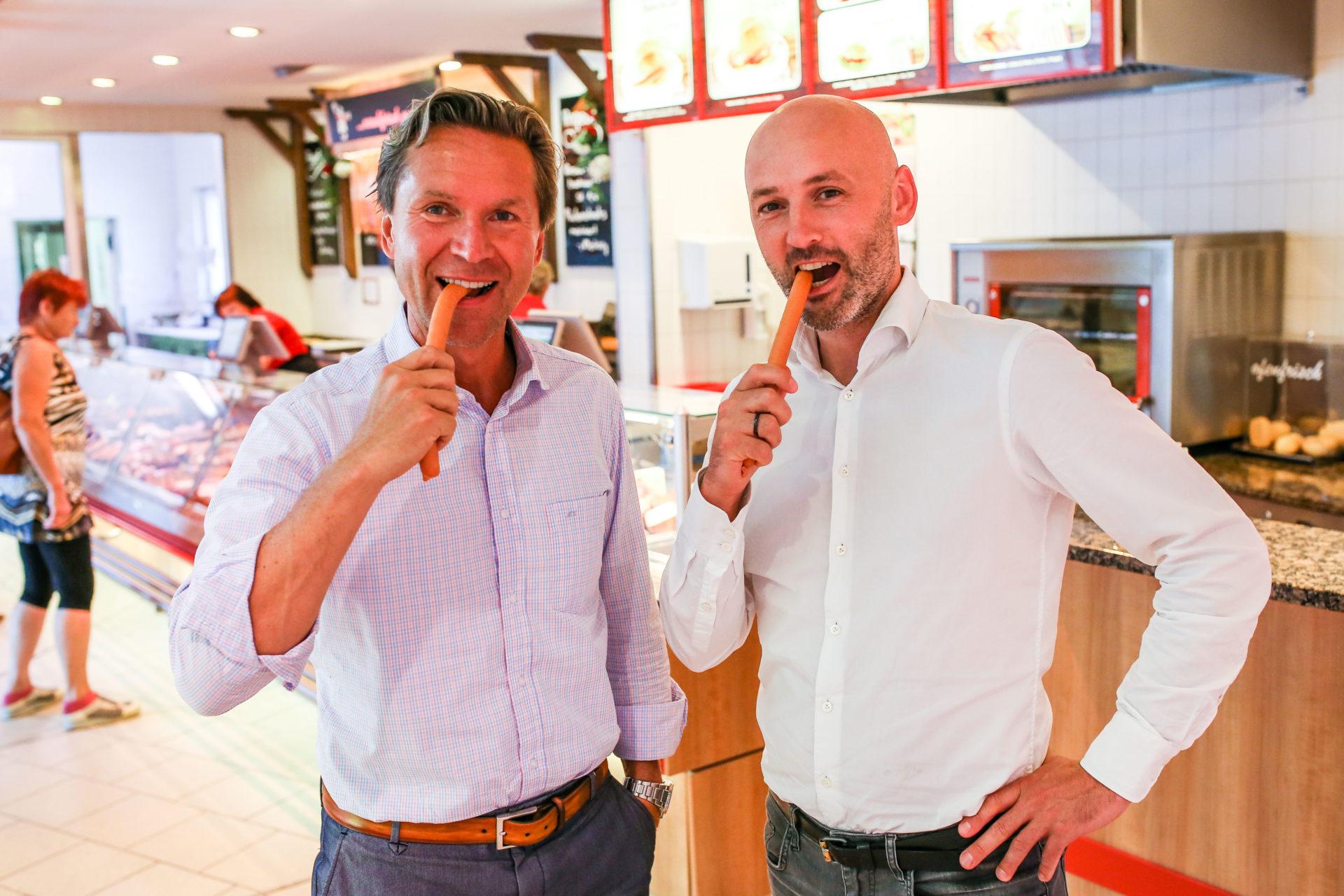 Michael Korch und Felix Alber stehen im Werksverkauf der Radeberger Produktionsstätte und beißen ins Würstchen