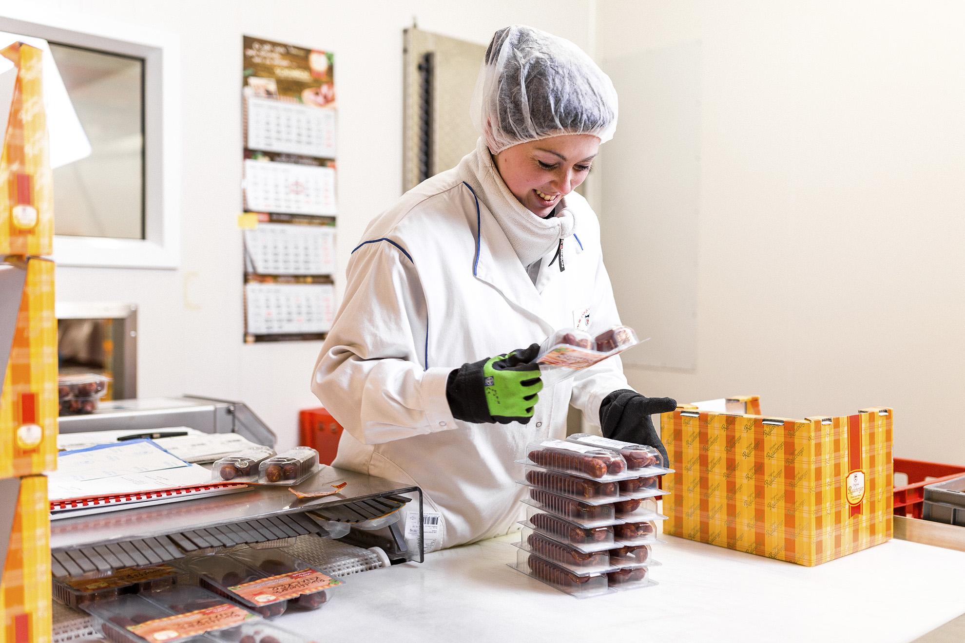 Junge Mitarbeiterin in der Verpackung konfektioniert Ware für den Supermarkt